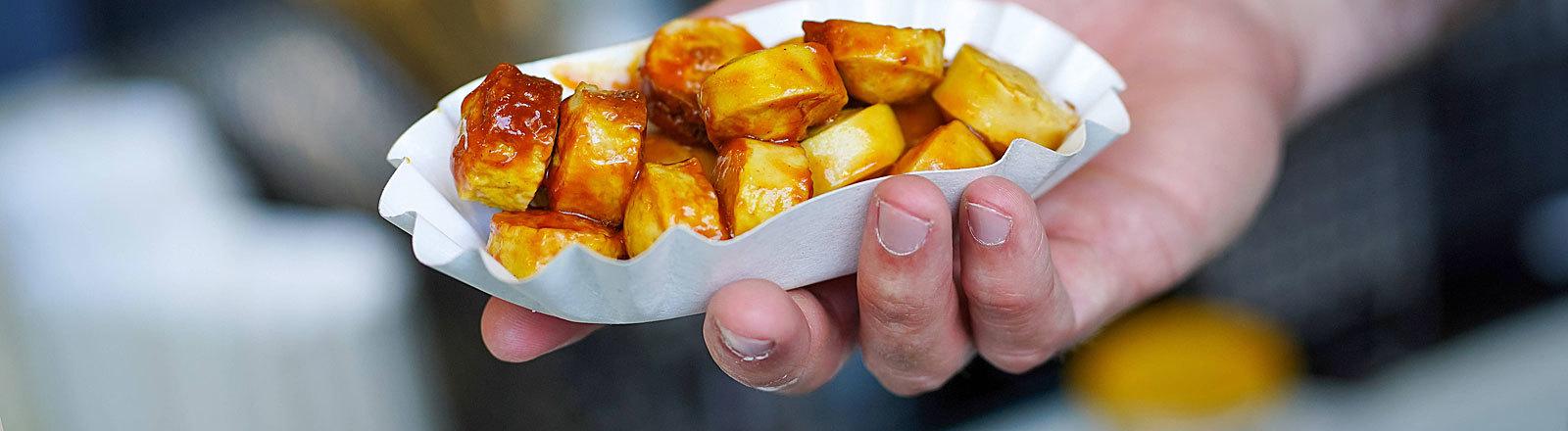 In einer weißen Schale liegt eine Currywurst. Die Schale wird von einer Hand in die Kamera gehalten.