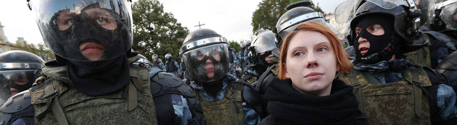 Bei einer Demonstration in Moskau steht eine junge Frau zwischen Polizisten. 10. August 2019.