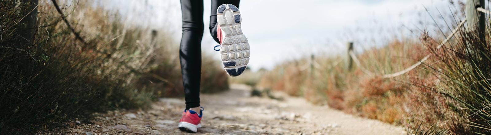 Eine Frau läuft auf einem Sandweg, die Schuhsohle des Laufschuhs ist deutlich erkennbar