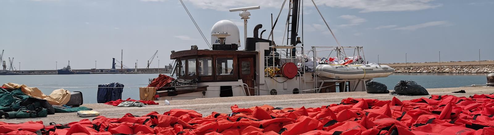 """02.09.2019: Das beschlagnahmte Rettungsschiff """"Eleonore"""" der deutschen Hilfsorganisation Mission Lifeline, liegt im Hafen, im Vordergrund liegt ein Teil der 104 Rettungswesten der geretteten Migranten"""