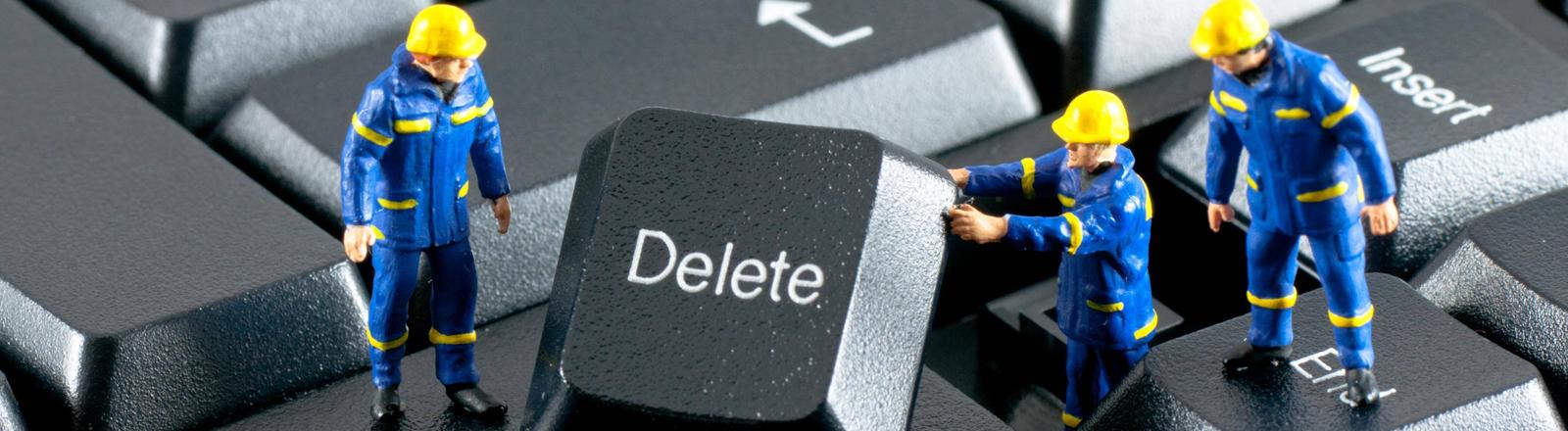 Spielzeugbauarbeiter heben eine Delete-Taste aus einer Tastatur