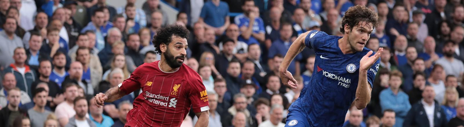 Liverpools Mohammaed Salah und Chelseas Marcos Alonso rennen nebeneinander her beim Premier League Spiel zwischen Chelsea und Liverpool am 22.9.2019