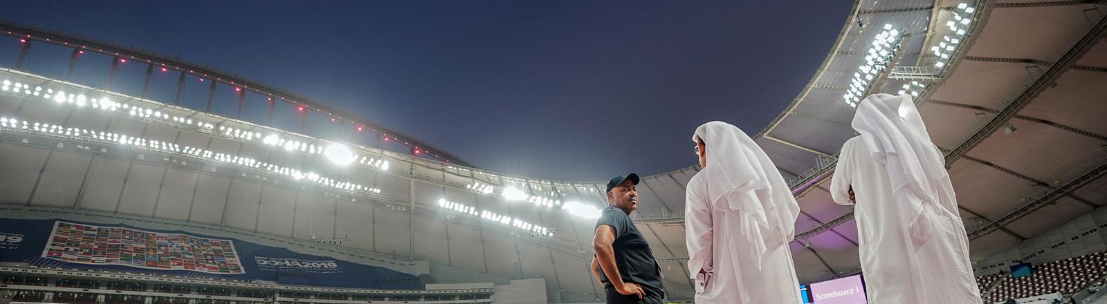 Männer in der traditionellen Bekleidung, dem «Thawb», stehen an der Laufbahn im Austragungsort der WM, dem Khalifa International Stadium