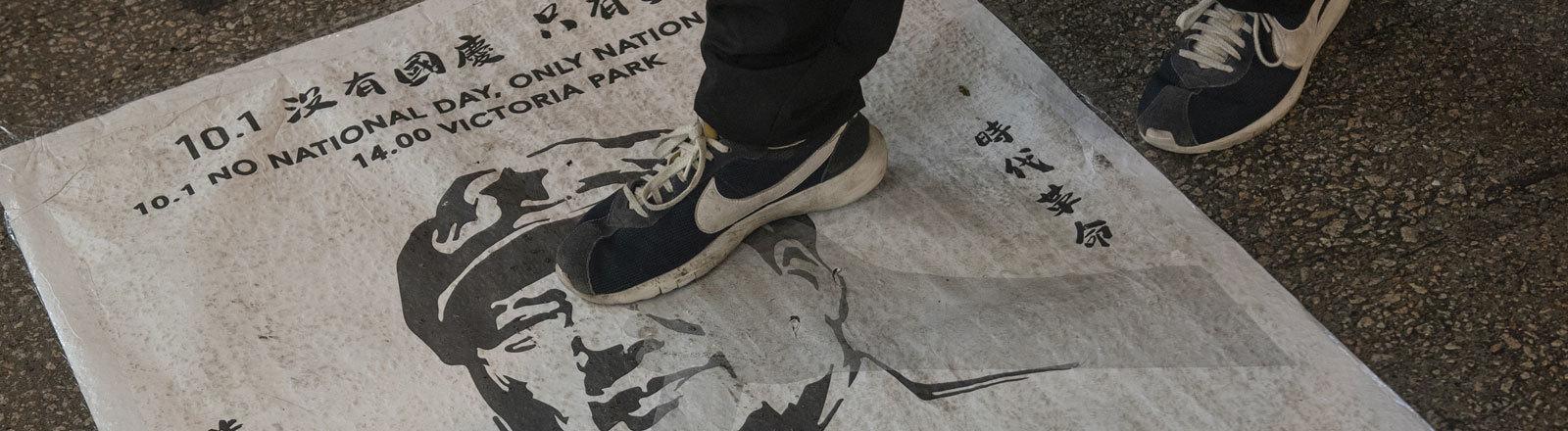 Proteste in Hongkong: Ein Plakat liegt auf dem Boden. Es zeigt Chinas Begründer Mao Zedong. Darauf steht ein Demonstrant mit seinen Schuhen (29.09.2019); Foto: dpa