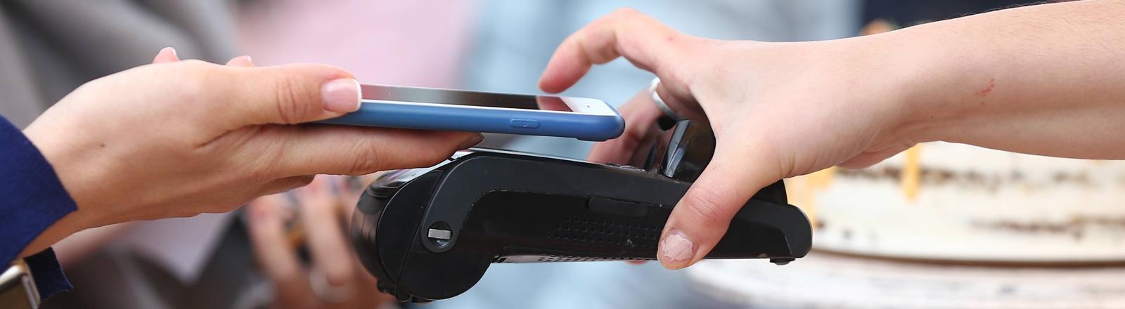 Ein Smartphone wird über ein Kartenlesegerät gehalten