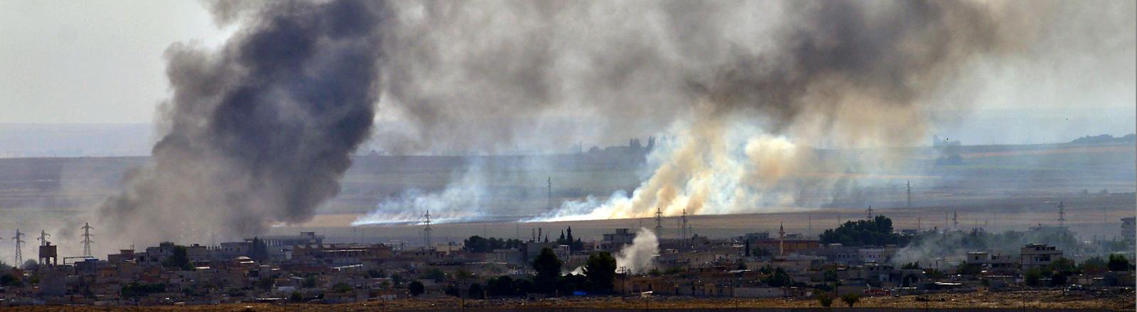 Rauchschwaden steigen auf über einer Stadt an der türkisch-syrischen Grenze