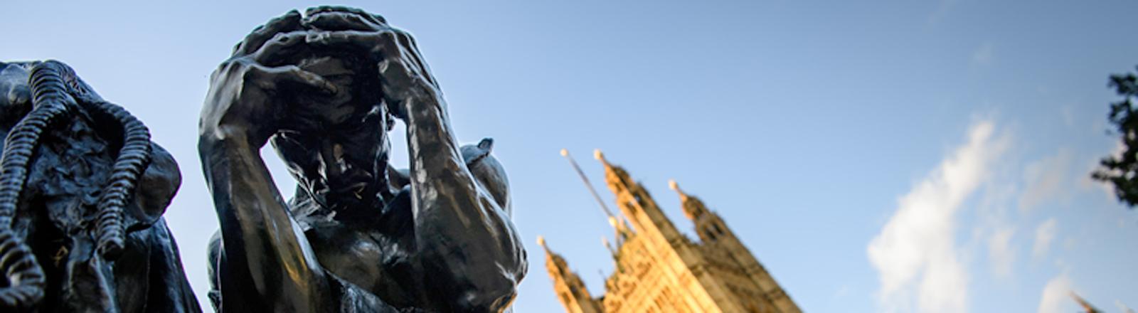 Der Palast von Westminster, davor Statuen von Rodin, die Sorge und Verzweiflung darstellen