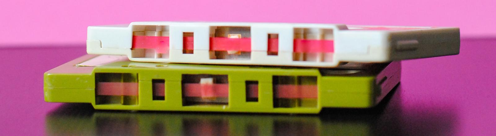 Zwei Musik-Kassetten auf einem pinken Tisch