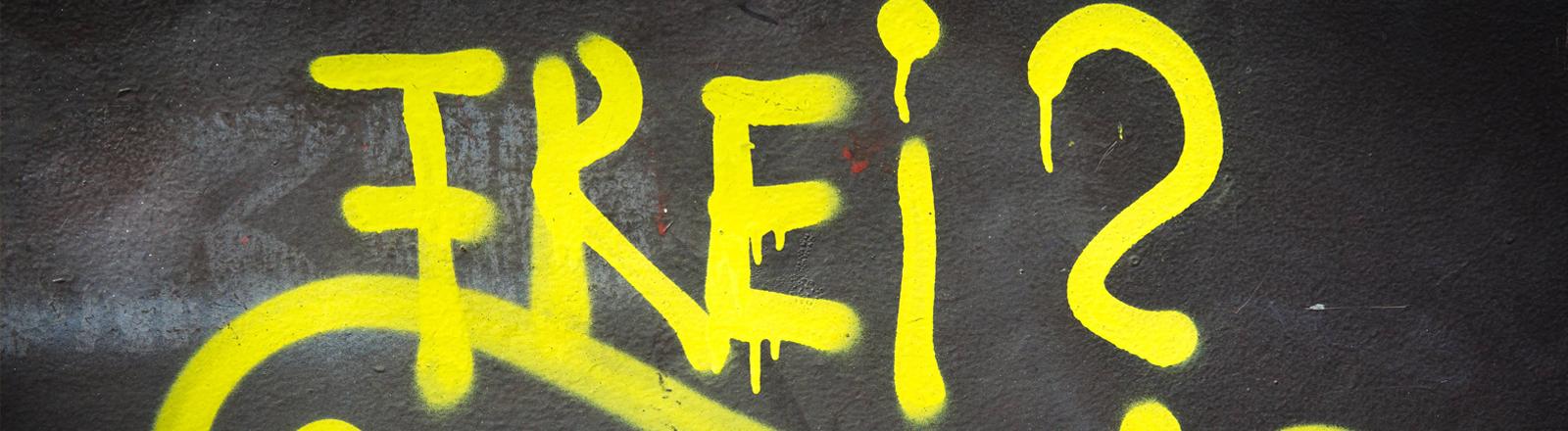 Das Wort Frei mit Fragezeichen als gelbes Graffito auf einer dunklen Wand.