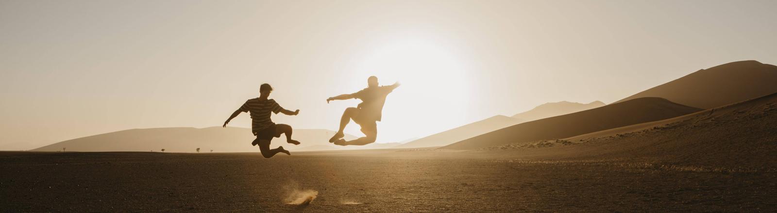 Zwei Männer springen durch die Wüste