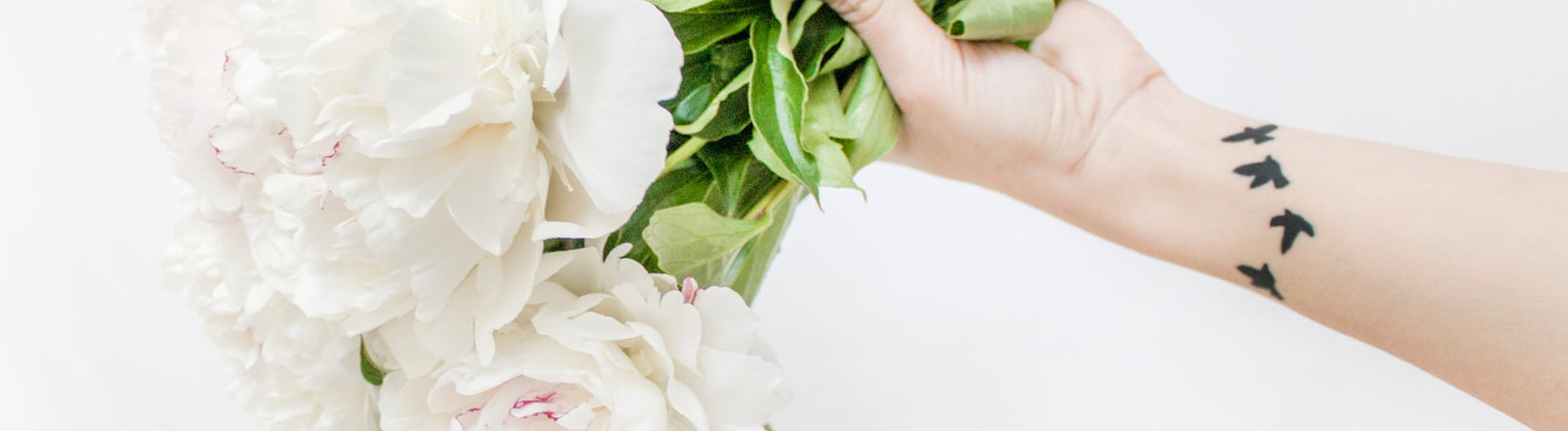 Tattoo am Handgelenk mit Blumen an der Hand
