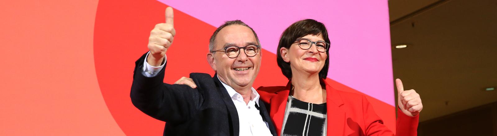 Norbert Walter-Borjans und Saskia Esken recken nach der Wahl die Daumen in die Luft.