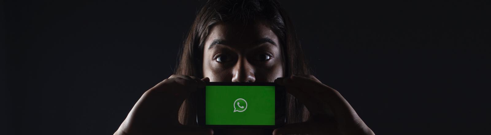 Eine Frau hält sich ein Smartphone mit einem Logo von Whatsapp vor den Mund