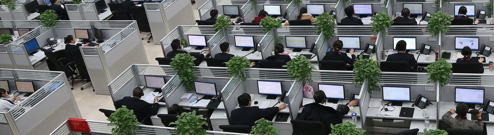 In einem Callcenter des Ministeriums der Bahn in China sitzen an vielen Schreibtischen Angestellte und arbeiten am Computer.