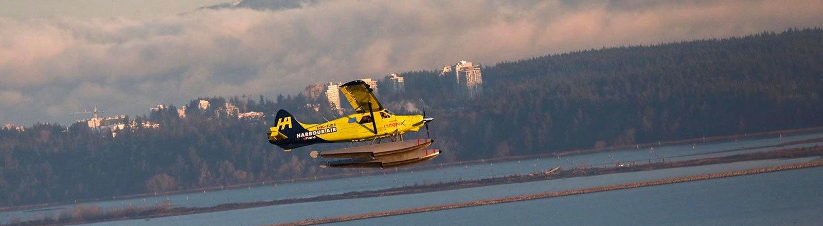 Das erste kommerzielle E-Flugzeug startet; es ist ein Wasserflugzeug mit E-Motor. Der Flug ist in Kanada, im Hintergrund verschneite Berge.
