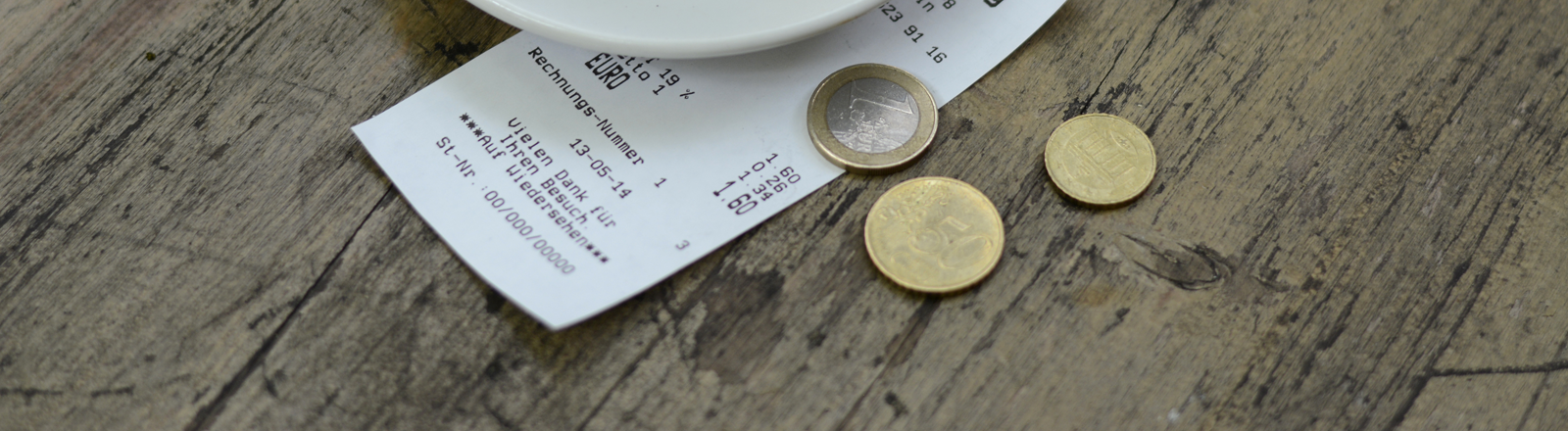 Unter einer Espresso-Tasse liegt ein Kassenbon, daneben Geld