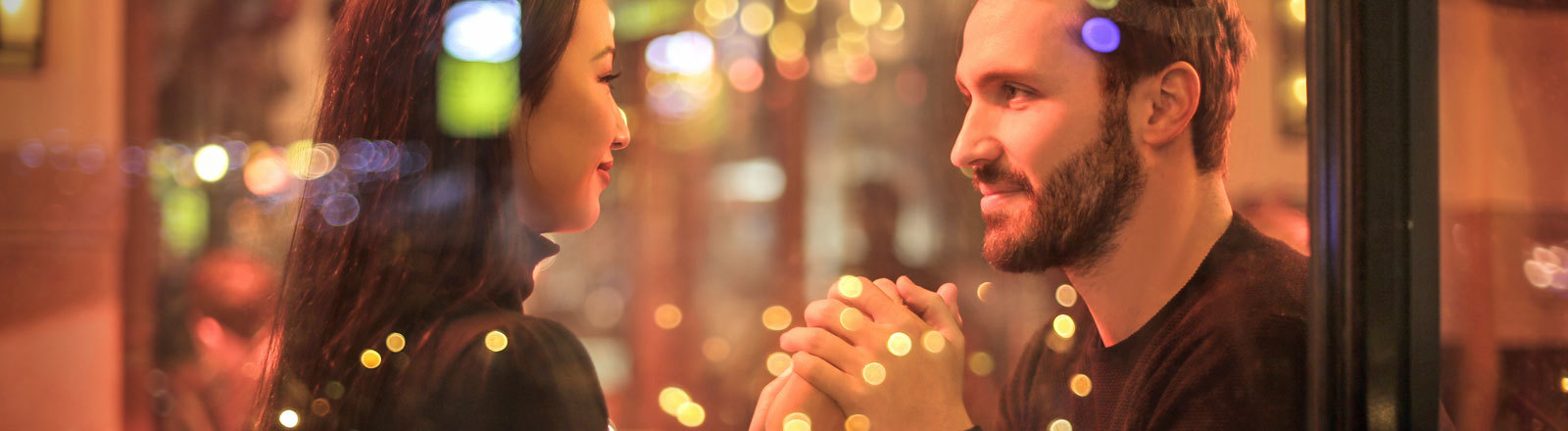 Ein Paar sitzt im Restaurant und hält die Hand, Sie schauen sich in die Augen. Wir blicken von draußen durch das Fenster drauf.
