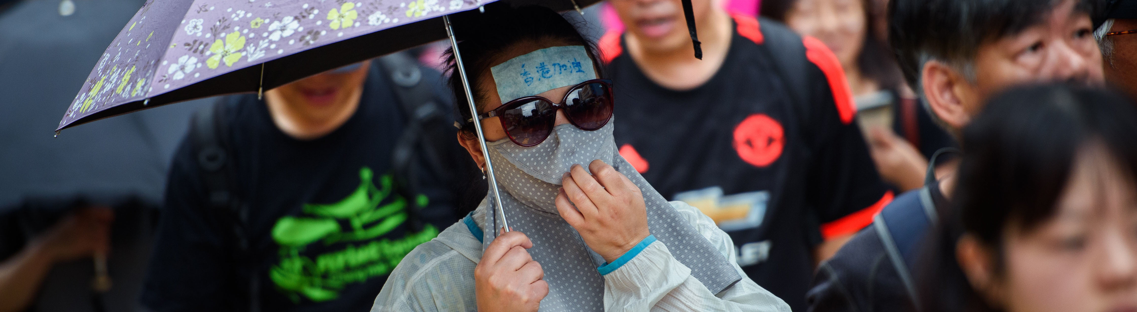 Vermummte Demonstrantin in Hongkong mit Regenschirm.