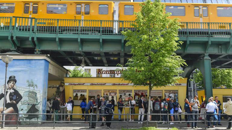 """Blick auf """"Konnopke's Imbiß"""" in Berlin an der Schönhauser Allee. Davor stehen Kunden Schlange. Der Imbiss ist unter der Hochbahn-Brücke einer U-Bahnlinie."""