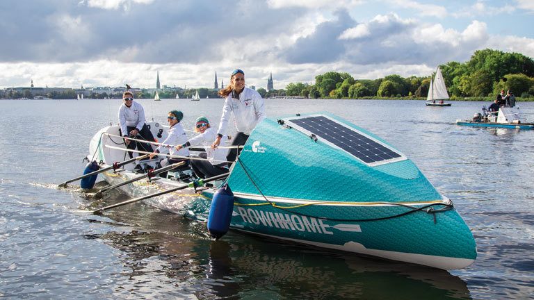 Auf einem modernen Ruderboot sitzen vier Frauen; sie rudern auf der Alster. Demnächst wollen sie den Atlantik überqueren.