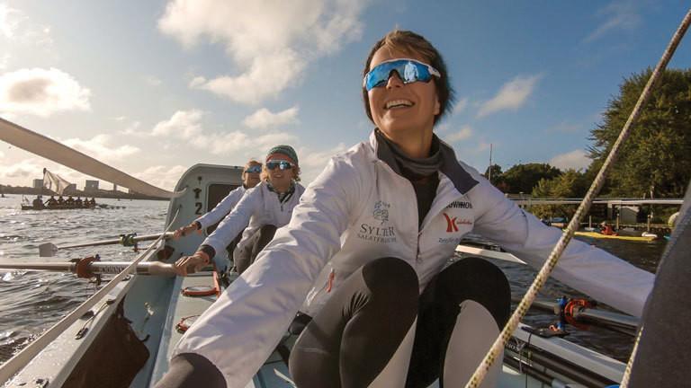 In einem Ruderboot sitzen drei Frauen; sie fahren mit ihrem Boot auf der Alster.