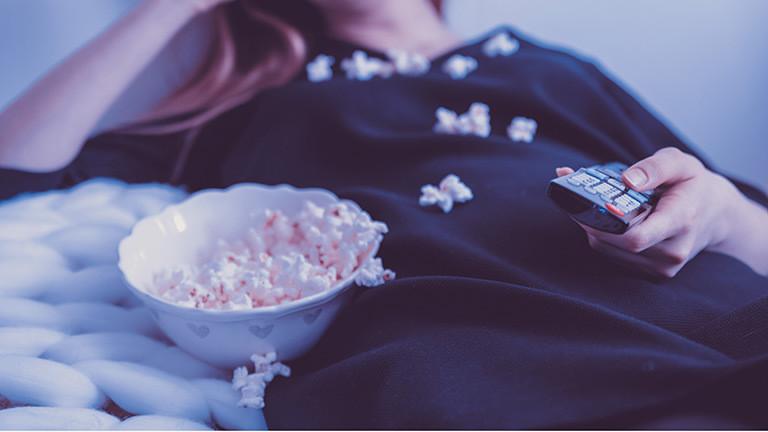 Eine Frau mit Popcorn und Fernbedienung