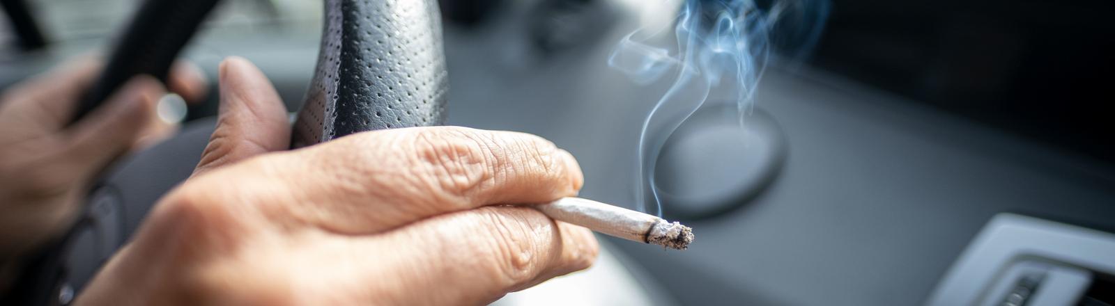 Ein Mann sitzt rauchend am Lenkrad eines Autos