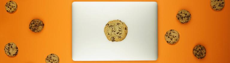 Ein Laptop, drumherum liegen Choclate Chips Cookies