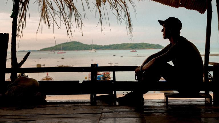 Tourist sitzt auf Terrasse in Thailand