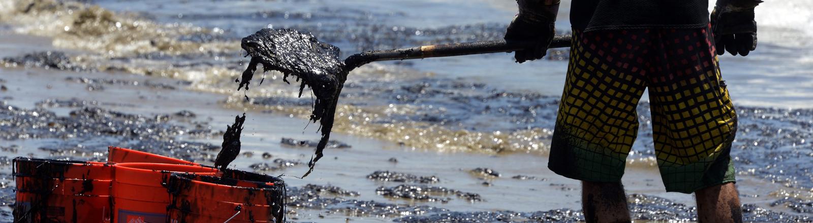 Ein Freiwilliger reinigt den Strand vor Santa Barbara von Öl.