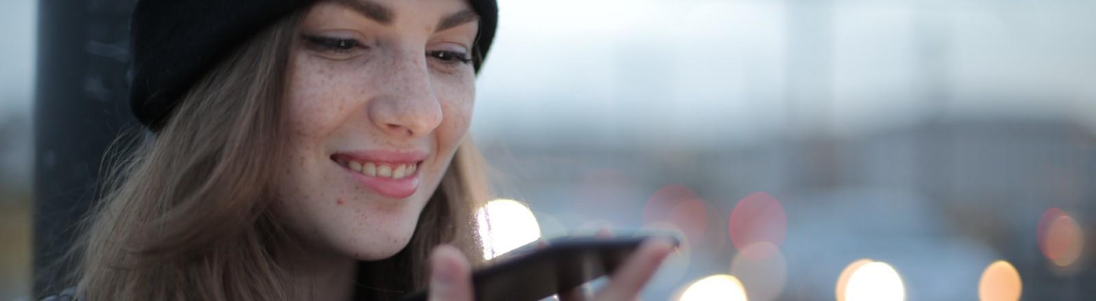 Frau spricht in Smartphone