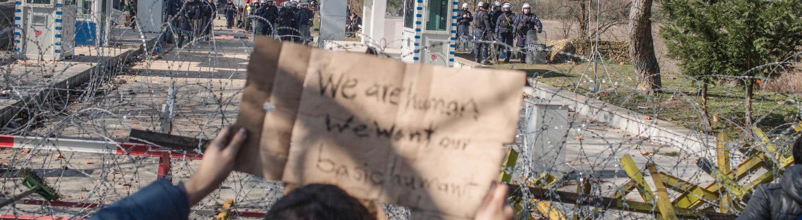 """Türkei, Pazarkule: Migranten stehen am bereits geschlossenen türkisch-griechischen Grenzübergang und halten ein Pappschild mit der Aufschrift """"We are human we want our basic humanity""""."""