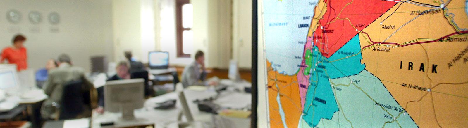 Eine Landkarte der Golfregion hängt im Krisenreaktionszentrum im Auswärtigen Amt in Berlin an der Wand, während Mitarbeiter des Sonderstabes Irak an ihren Arbeitsplätzen sitzen.