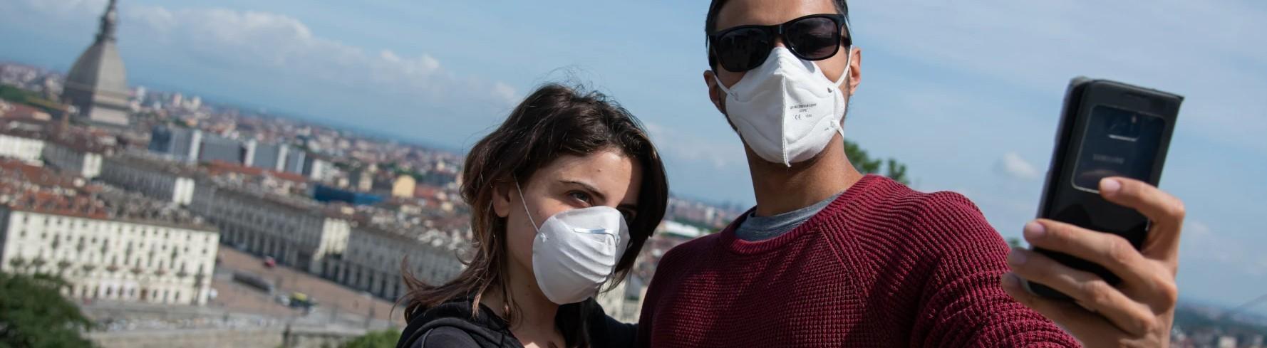 Ein Paar in Turin trägt einen Mundschutz und macht ein Selfie.