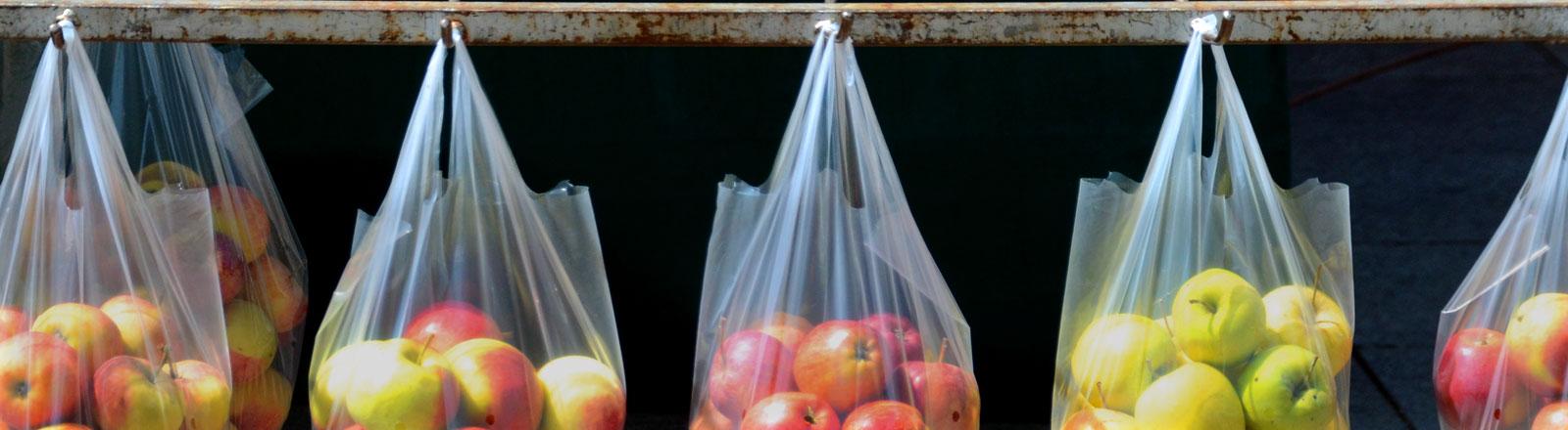Mehrere Plastiktüten mit Äpfeln hängen  in einer Reihe.