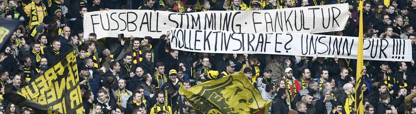 BVB Fans im eigentlichen Gästeblock auf der Nordtribüne des Stadions mit Spruchbändern.