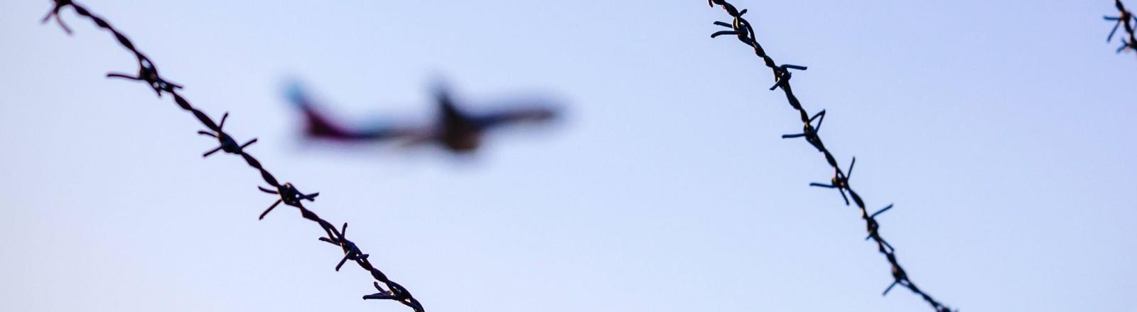 Ein Flugzeug ist im Himmel, davor ist Stacheldraht.