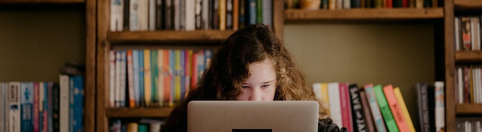Ein Teenager sitzt vor ihrem Computer.