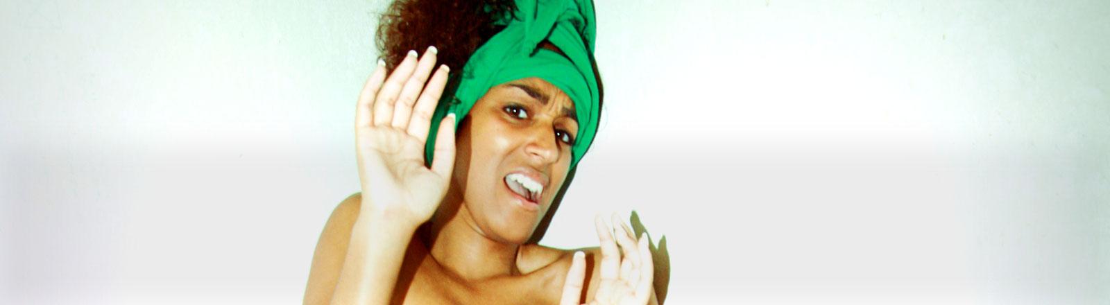 Eine Frau mit grünem Tuch in den Haaren macht eine abwehrende Bewegung.