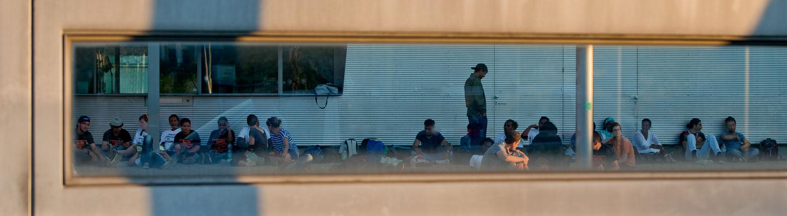 Flüchtlinge sitzen in einem Hof des Bundesamts für Migration und Flüchtlinge. Sie wurden durch eine Tür fotografiert.