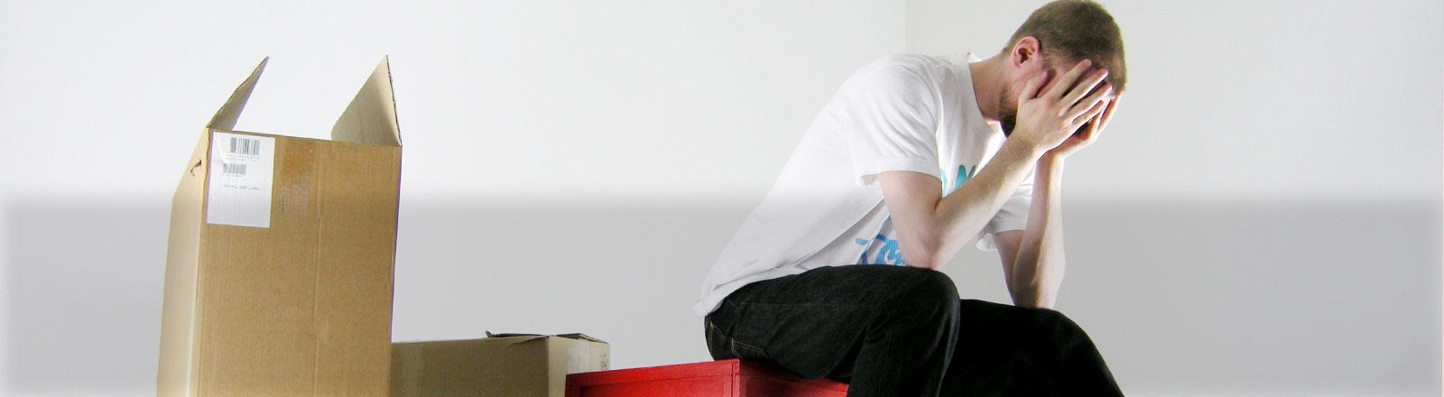 Ein Mann sitzt auf gepackten Kartons und stützt seinen Kopf in seine Hände.