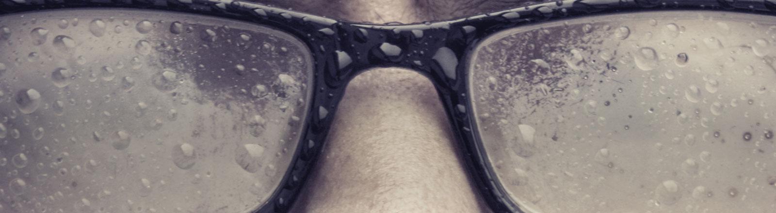 Eine beschlagene Brille auf einer Nase.