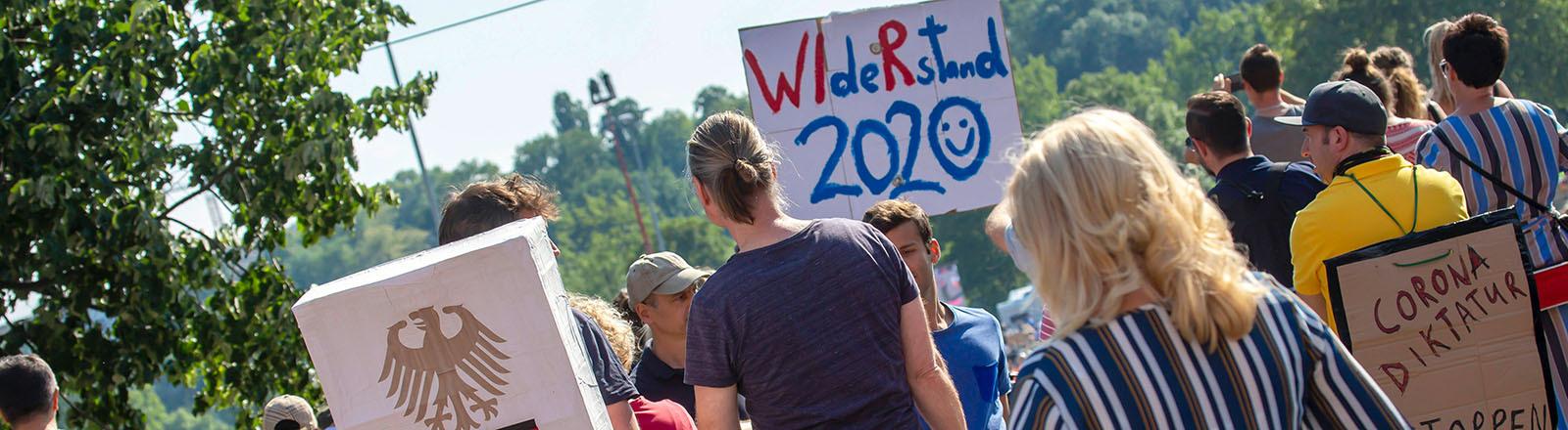 """In Stuttgart demonstrieren Menschen gegen Corona-Beschränkungen. Auf einem Schild steht """"Widerstand 2020"""", auf einem anderen """"Corona Diktatur"""" (16.05.2020)"""