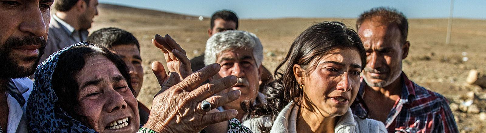 Nachdem ein Familienmitglied bei den Kämpfen mit den IS-Milizen ums Leben kam, ringen kurdische Angehörige in Suruc/Türkei am Grenzübergang nach Kobane/Syrien um Fassung.