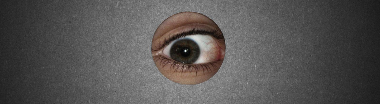 Ein Auge schaut durch ein kreisrundes Loch.
