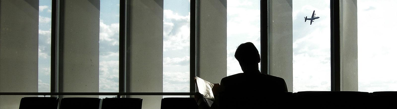Ein Mann liest am Flughafen Zeitung, im Hintergrund startet ein Flugzeug.