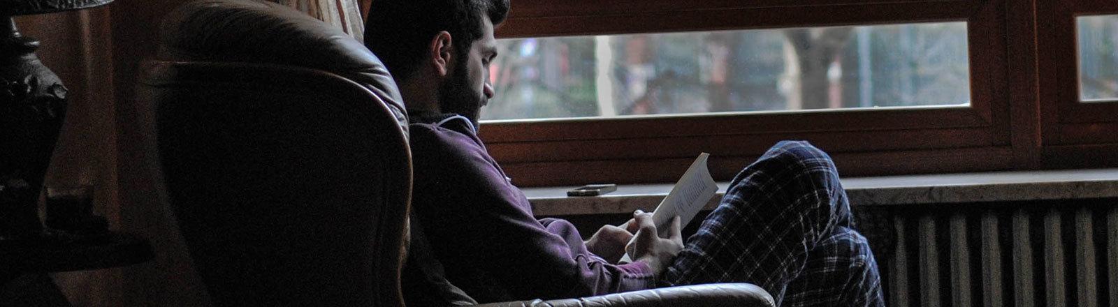 Ein Mann sitzt auf einem Sessel vor dem Fenster, er liest.