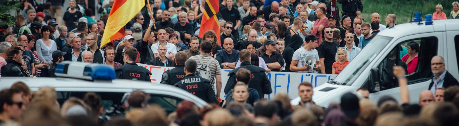Gegner der Flüchtlingsunterkunft stehen am 26.06.2015 in Freital (Sachsen) in der Nähe des ehemaligen Leonardo-Hotels, das jetzt als Flüchtlingsheim dient.