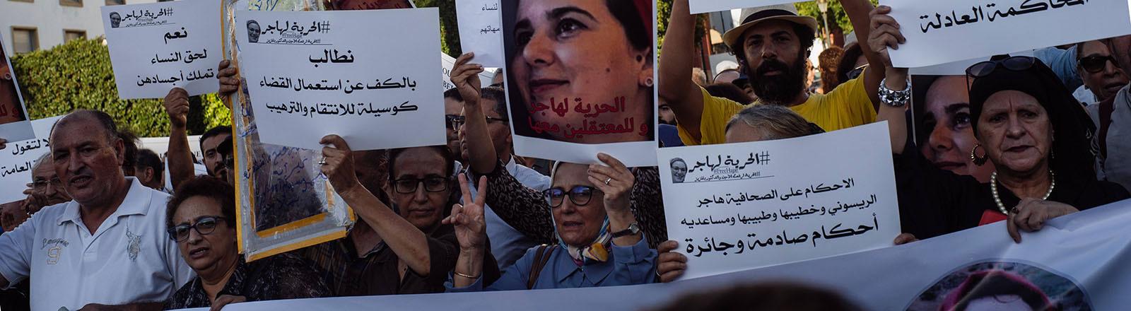 In Rabat, Marokko, fordern Demonstranten die Freilassung der Journalistin Hajar Raissouni; sie halten unter anderem Fotos von ihr in die Luft (02.10.2019)