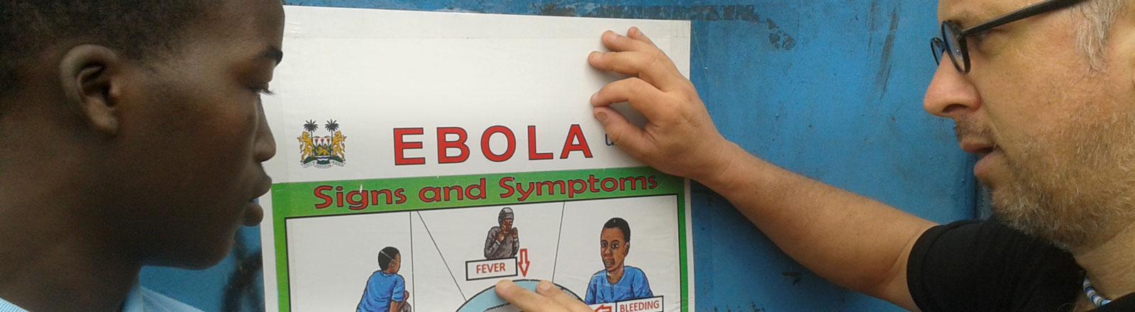 Zwei Männer stehen vor einer Ebola-Informationstafel.